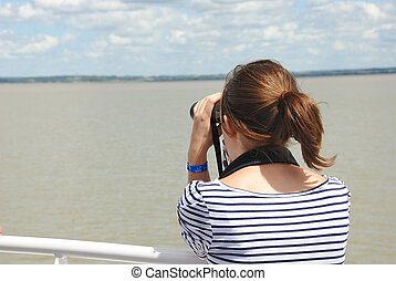 Girl looking at the river with binoculars