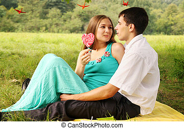 Cute young couple talking on the grass