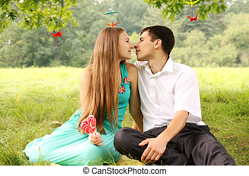 gentle kiss of a young couple on a picnic