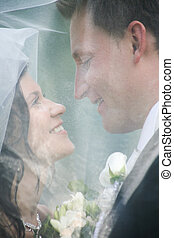 Love - Face of newly wedded looking at each other under veil...