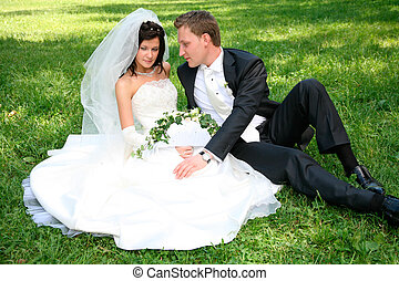 Couple on the grass - Portrait of happy couple sitting on...