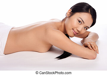 Beautiful topless Asian woman lying on her stomach on the...