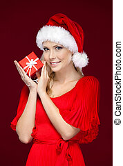Beautiful woman in Christmas cap hands a gift