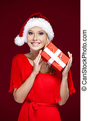 Pretty woman in Christmas cap hands a present