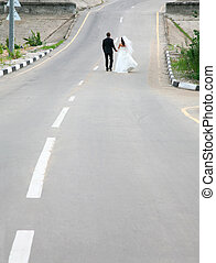 Future - Conceptual image of newlyweds walking on road...
