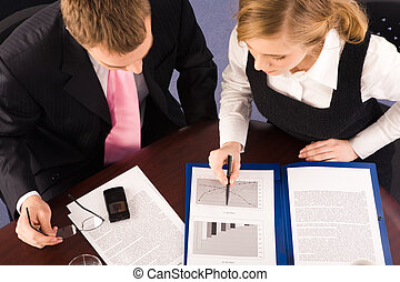 Paperwork - View from above of business partners sitting at...