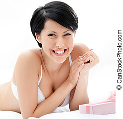 Woman in underwear finds a present in bed, white background