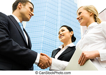 Business handshake of two successful partners at modern...