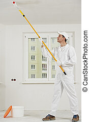 house painter at work with painting roller - painter worker...