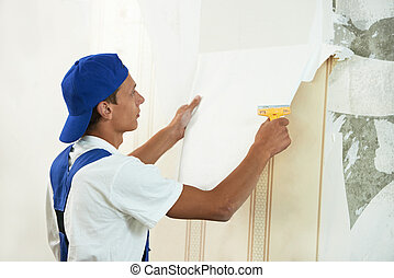 painter worker peeling off wallpaper - One painter worker...