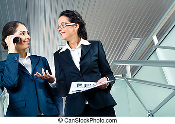 Partners - Portrait of successful woman talking to another...