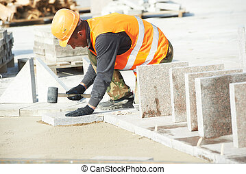 sidewalk pavement construction works - mason worker making...