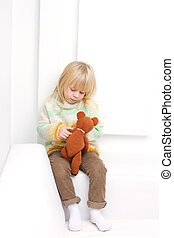 Little Girl 3 years with a brown teddy bear sitting on a...