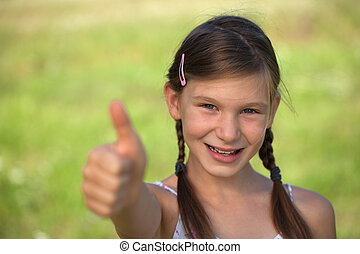 Young girl giving thumbs up - Happy smiling young girl with...