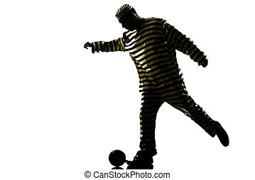 man prisoner criminal playing soccer with chain ball - one...