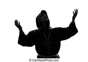 man monk priest silhouette praying - one caucasian man...