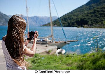 Woman takin a photo of yacht