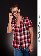 Fashion young man holding his fashionable sunglasses