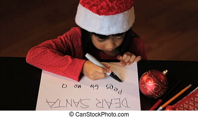 Asian Girl Writing Santa Claus - A cute six year old Asian...