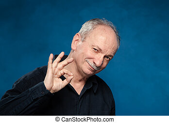 elderly man showing ok sign