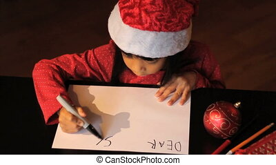 Girl Writes Dear Santa - A cute six year old Asian girl...