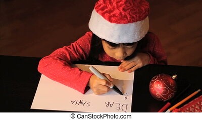 Girl Writing Santa Claus - A cute six year old Asian girl...