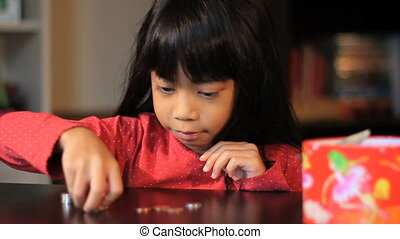 Girl Counting Money - A cute little six year old Asian girl...