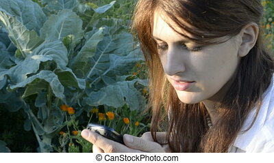 Young woman in the garden dials the phone