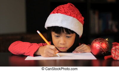 Six Year Old Writing Santa Claus - A cute six year old Asian...
