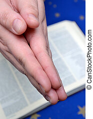 Praying hands and a bible