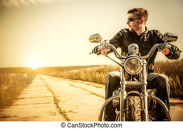 Biker man sits on a bike