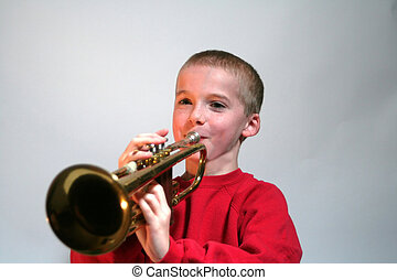 Smiling Boy Playing Trumpet - Smiling young boy playing the...
