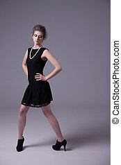 beautiful young woman with elegant black dress, studio shot