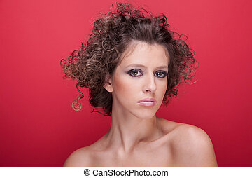 young and beautiful woman, with curly hair, on red background, studio shot