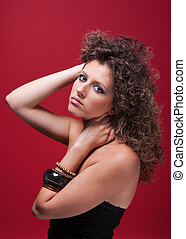 young and beautiful woman, with curly hair, holding her neck, on red background, studio shot