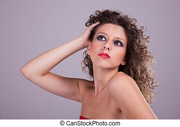 beautiful woman with curly hair, holding the hair, studio shot