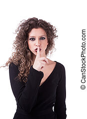 Beautiful young woman asking for silence, with curly hair, isolated on white background. Studio shot.