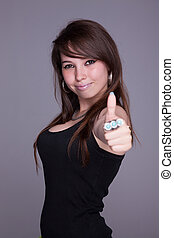 beautiful and happy young woman, with tumb up, studio shot