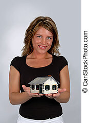 Home Ownership - Young woman holding house symbolizing home...