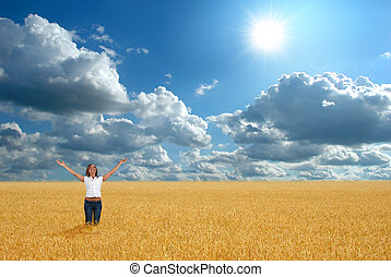 Freedom - Woman with arms raised agaisnt a bright cloudscape...