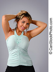 Woman Modeling - Woman modeling with arms behind head over a...