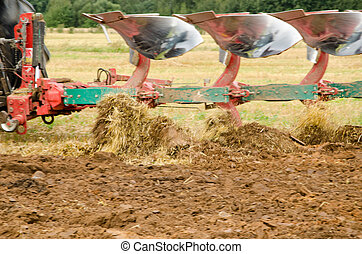 Closeup tractor plough plowing agricultural field - Closeup...