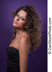 young and beautiful woman, with curly hair, on purple background, studio shot