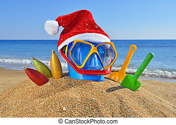 Christmas toys, decorations and Santas hat on the beach...