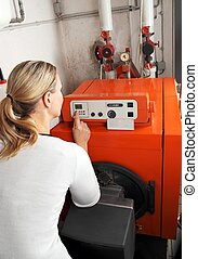Woman adjusting the heating in the Boiler room - Woman...
