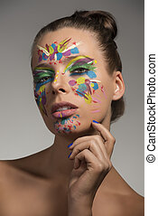 pretty girl with abstract make-up on the face, she looks in to the lens and her right hand is near the chin