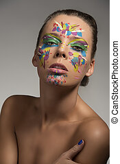 pretty girl with abstract make-up on the face, she looks in to the lens with sensual expression and her right hand is near the left shoulder