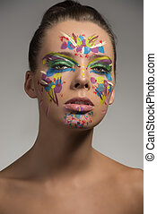 pretty girl with abstract make-up on the face, she is in front of the camera and looks in to the lens
