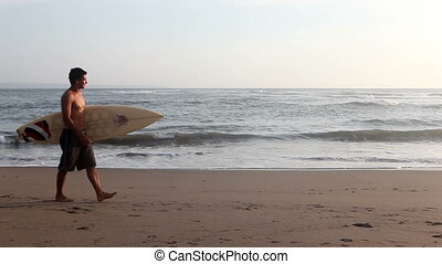 Surfer with surf board walking on beach and looking at ocean...