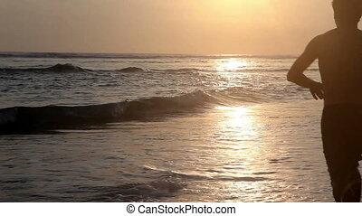 Water sport - Surfer running into ocean and surfing while...